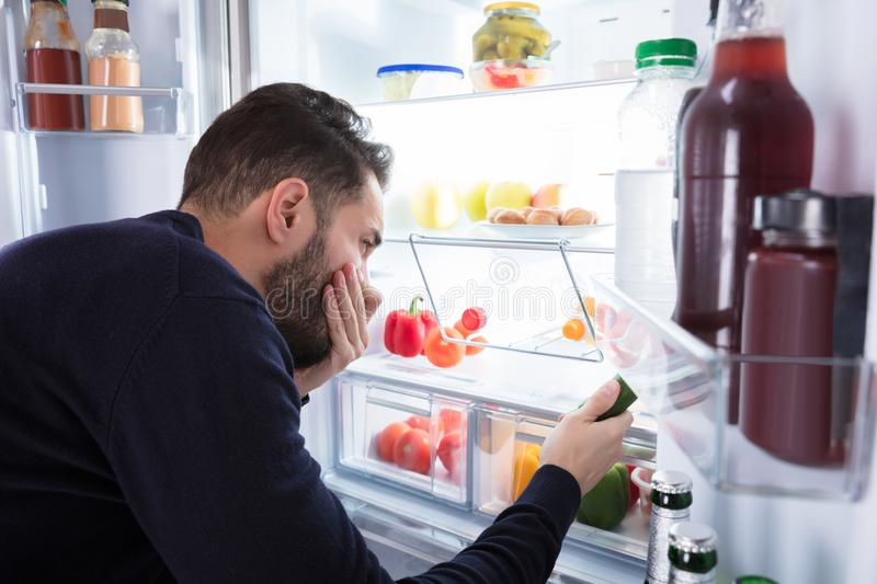 Man Noticing Smell Coming From Foul Food In Refrigerator. Close-up Of A Young Man Noticing Smell Coming From Foul Food In Refrigerator royalty free stock image