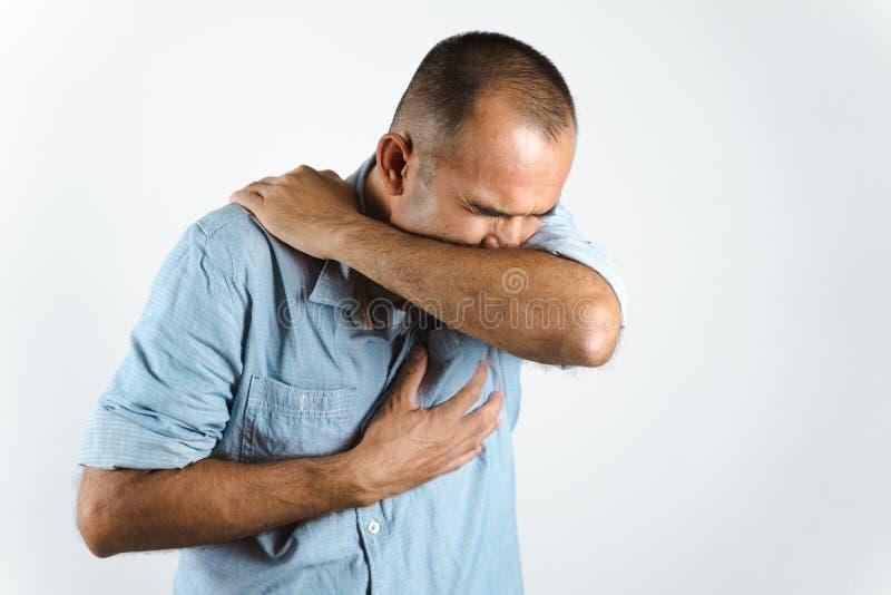 Man nyser eller hostar i armbågen för att förhindra spridning av viruset COVID-19 eller Corona Virus mot vit bakgrund. royaltyfria foton