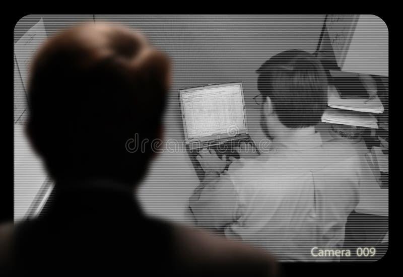 Man observera ett anställdarbete via enströmkrets videomonito royaltyfria bilder