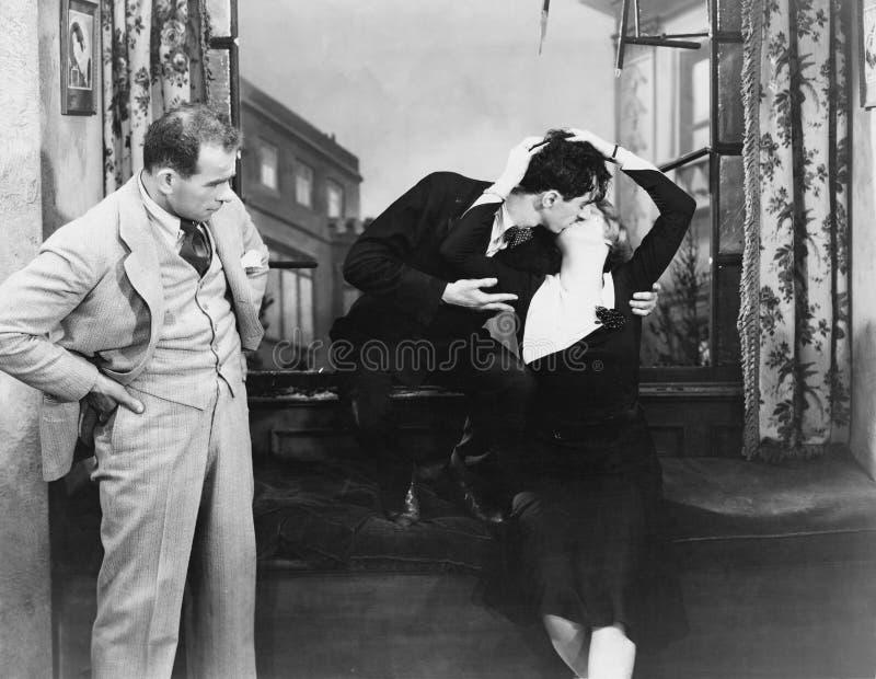 Man observera kyssande par (alla visade personer inte är längre uppehälle, och inget gods finns Leverantörgarantier att det ska g arkivbilder