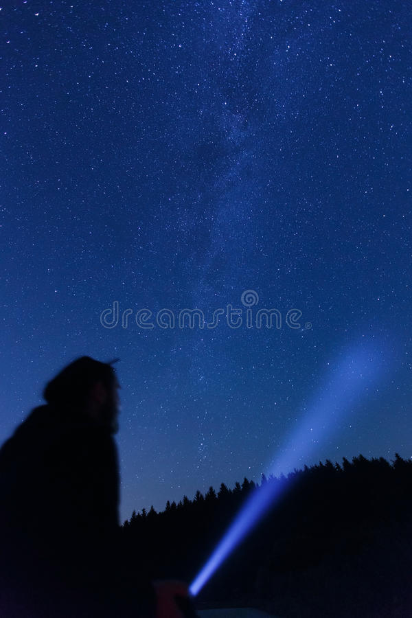 Man observing beautiful, wide blue night sky with stars. Silhouette of a man with a flashlight, observing beautiful, wide blue night sky with stars and visible royalty free stock image
