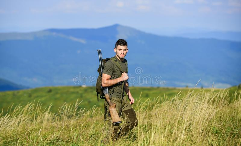 Man observing nature background. Hunter hold rifle. Hunting equipment. Hunter handsome guy with weapon. Brutal masculine royalty free stock image