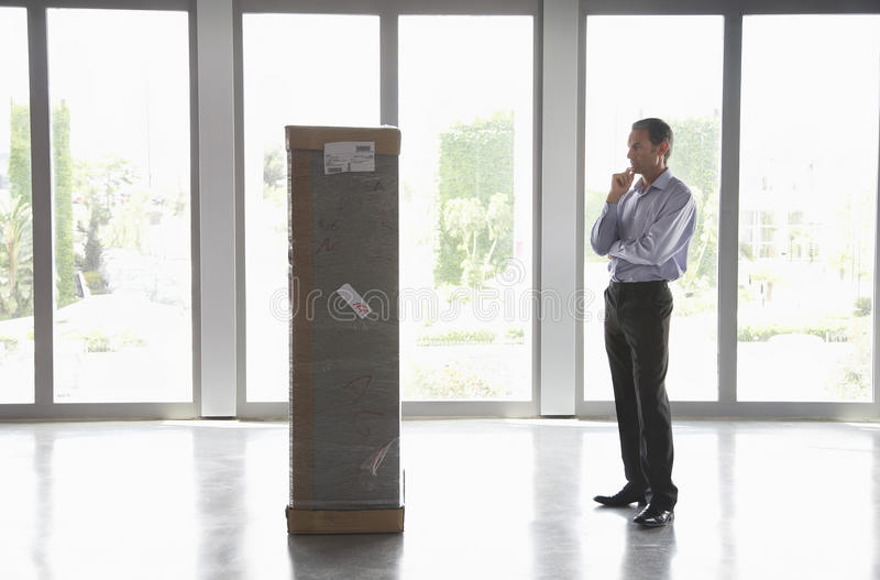 Man Observing Package In Empty Office. Full length side view of a man with hand on chin observing package in empty office royalty free stock photos