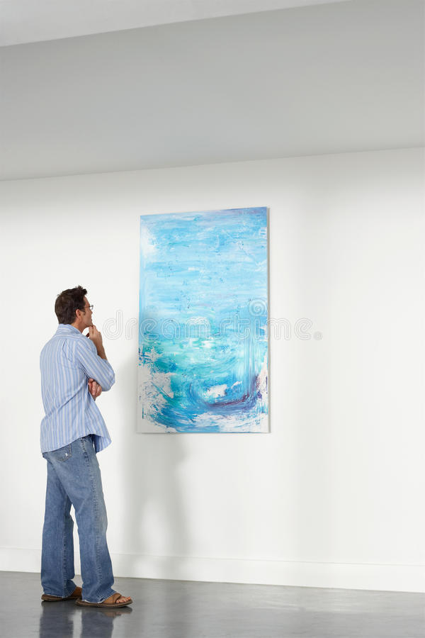Man Observing Painting In Art Gallery. Full length of man observing painting in art gallery royalty free stock image