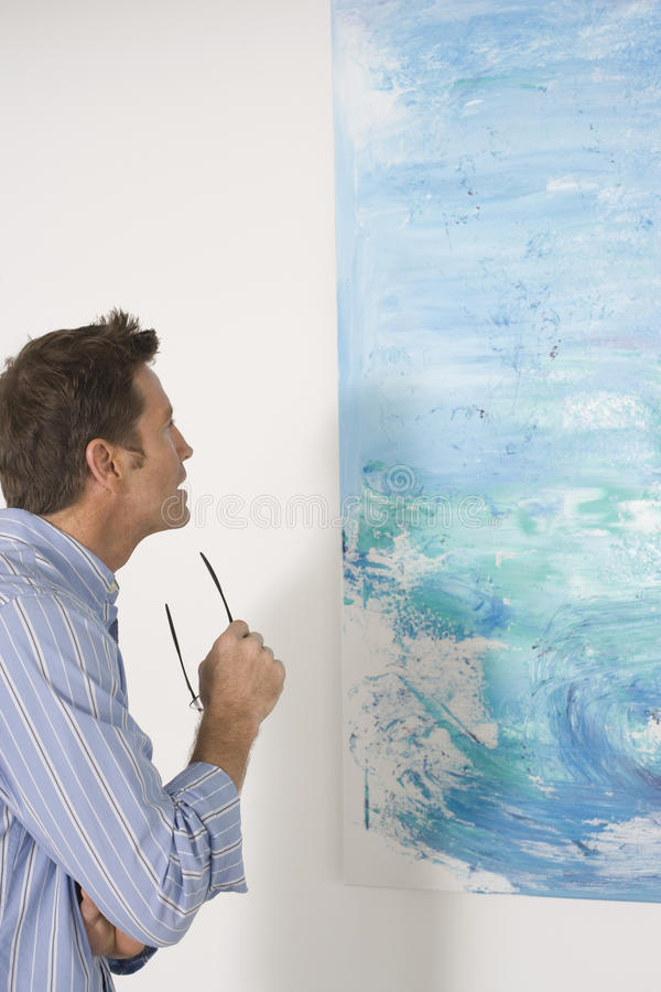Man Observing Painting In Art Gallery. Side view of man observing painting in art gallery royalty free stock photo