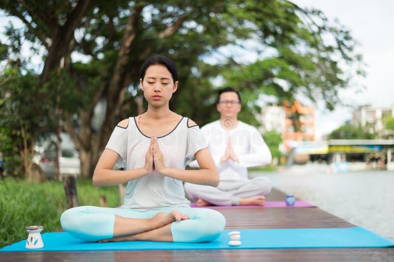 Man och övande yoga och meditation för kvinna på den matta nära floden royaltyfri fotografi