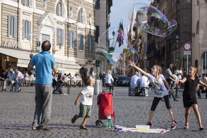 Man och barn med stora såpbubblor royaltyfria bilder