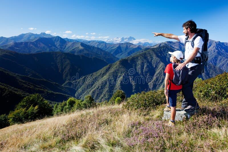 Man och barnpojke som plattforer i en bergäng arkivfoton
