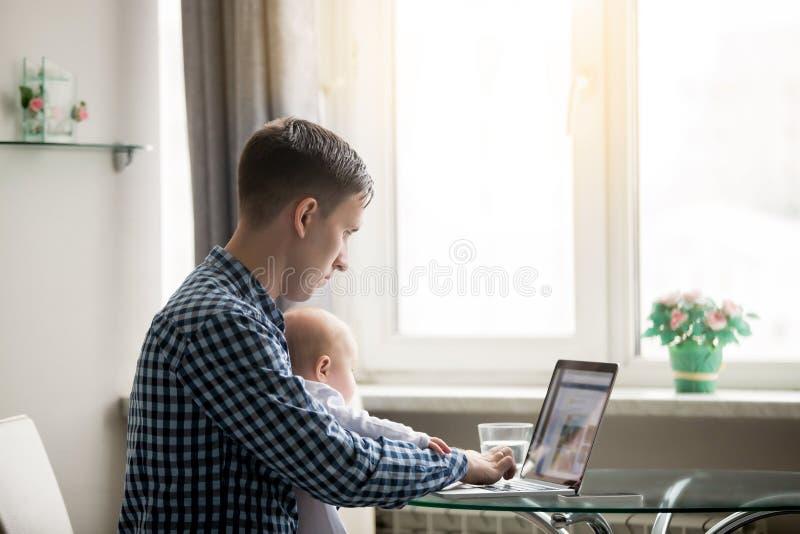 Man och en behandla som ett barn på bärbara datorn royaltyfria bilder
