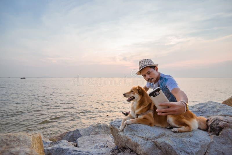 Man och en hund som tillsammans sitter på stenen nära havet royaltyfria foton