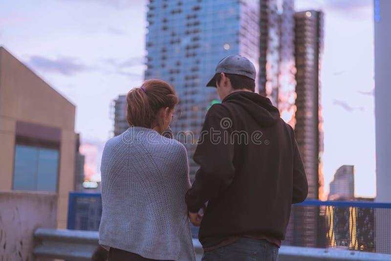 Man och ett kvinnligt anseende på ett tak av en byggnad och att diskutera något royaltyfria bilder