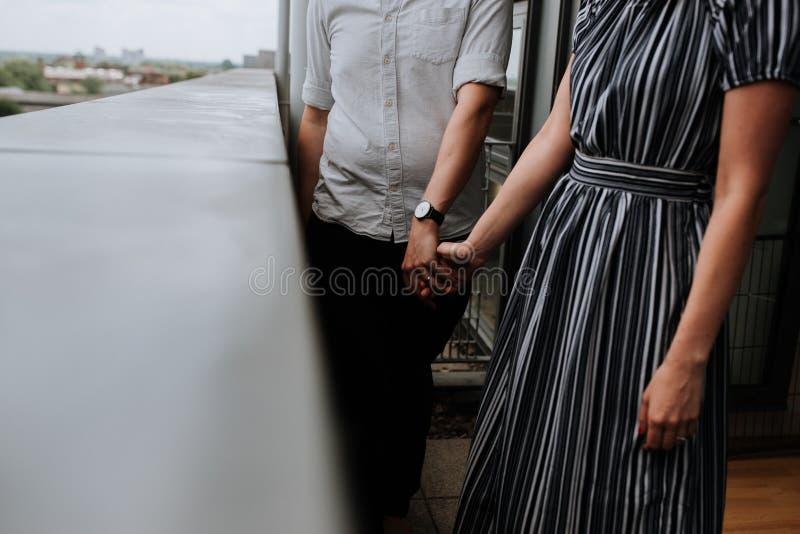Man och ett kvinnligt par som rymmer händer som står i balkongen arkivfoto