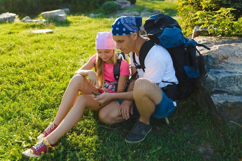 Man och flicka med ryggsäcken som vilar och ser kompasset fotografering för bildbyråer