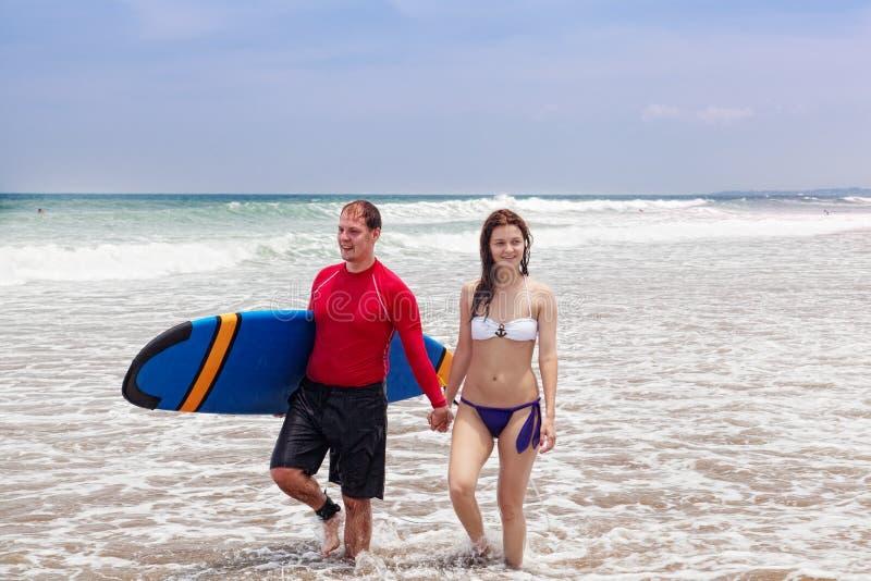 Man och flickan med en surfingbräda royaltyfri fotografi