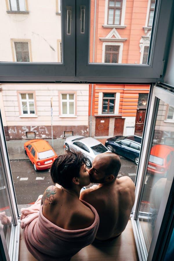 Man och härlig flicka, medan sitta vid fönstret royaltyfri bild