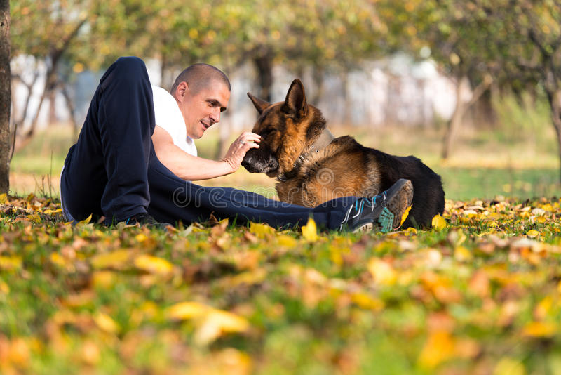 Man och hans tyska herde för hund arkivfoto