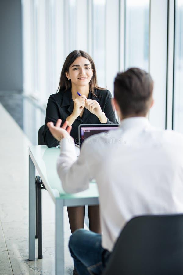 Man och kvinna för affärsfolk som har möte på tabellen i modernt kontor mot panorama- fönster Fokus på kvinna fotografering för bildbyråer