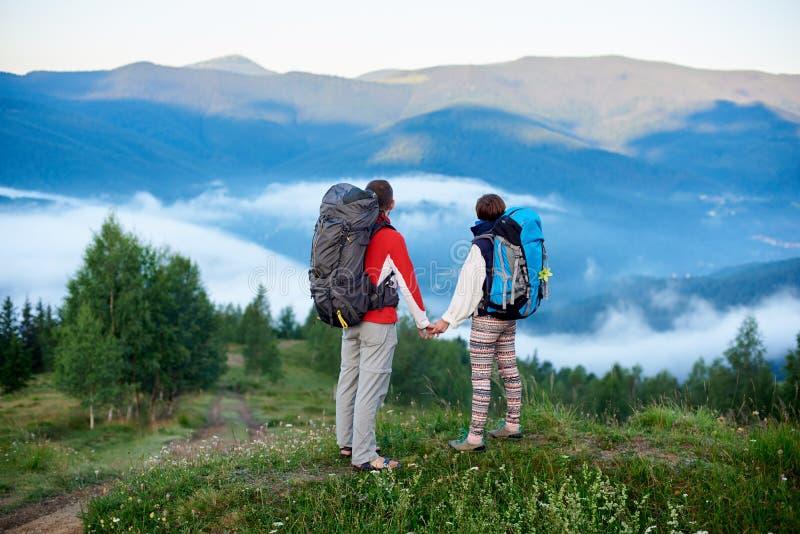 Man och kvinna för bakre sikt med ryggsäckar som överst rymmer händer av kullen med sikt av berg royaltyfria bilder