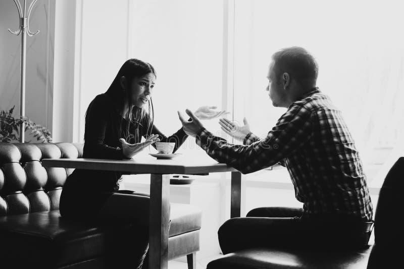 Man och kvinna i diskussioner i restaurangen arkivfoto