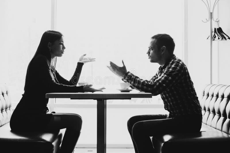Man och kvinna i diskussioner i restaurangen royaltyfria bilder