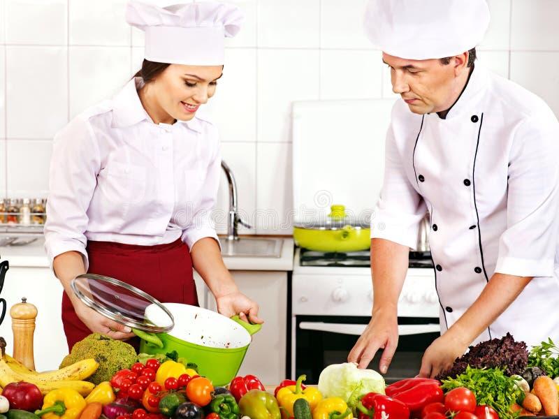 Man och kvinna i kockhattmatlagning. royaltyfri bild