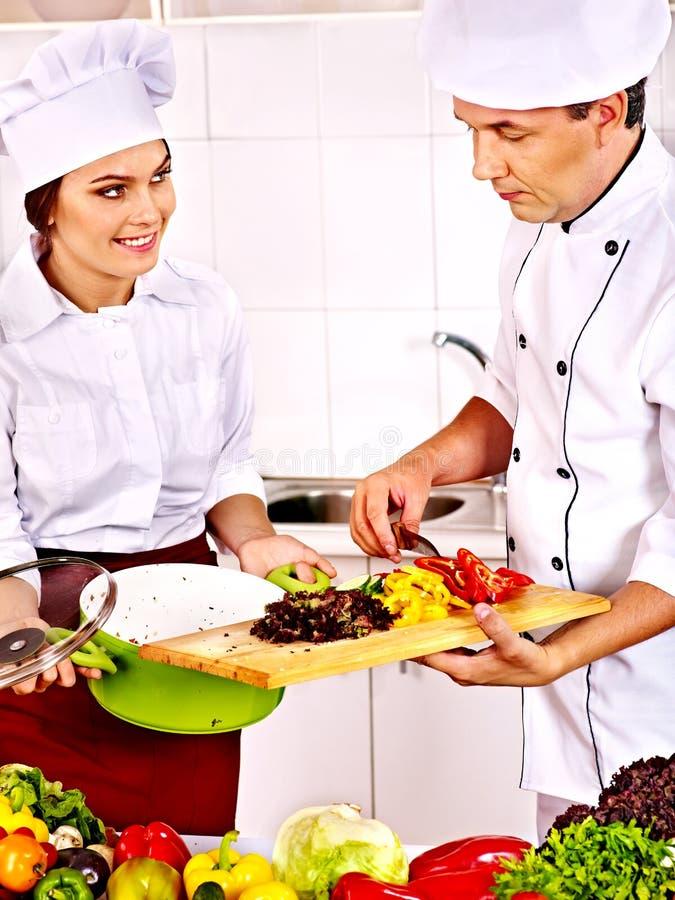 Man och kvinna i kockhattmatlagning. royaltyfria bilder