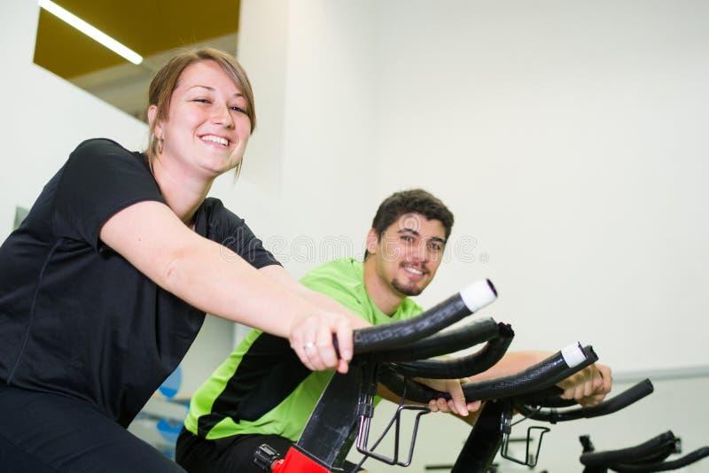 Man och kvinna med den stationära cykeln i idrottshall arkivbilder