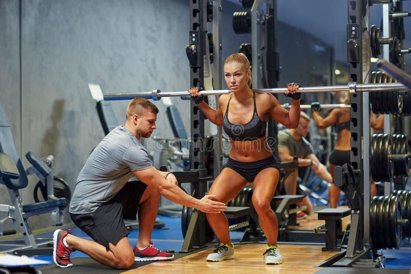Man och kvinna med skivstången som böjer muskler i idrottshall royaltyfri fotografi