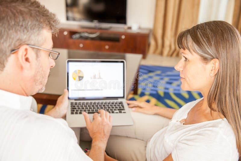 Man och kvinna på en soffa med bärbara datorn arkivbilder