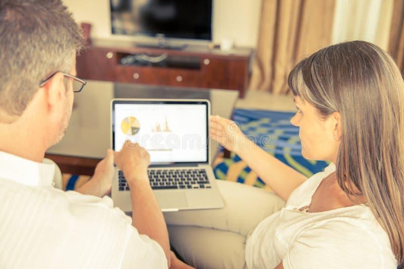 Man och kvinna på en soffa med bärbara datorn royaltyfri bild