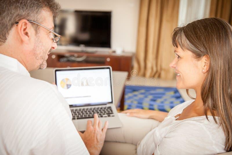 Man och kvinna på en soffa med bärbara datorn royaltyfria bilder