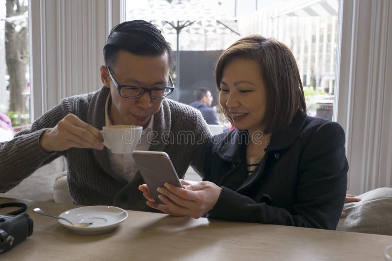 Man och kvinna på kafét som ser telefonen arkivfoto