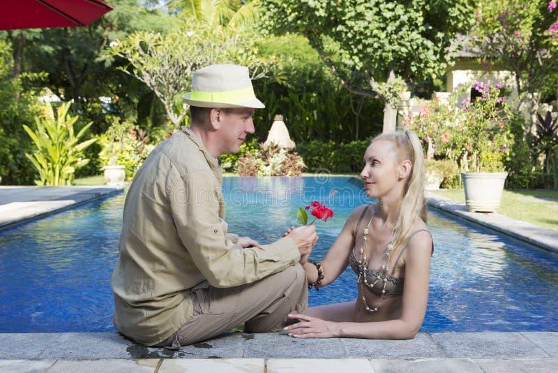 Man och kvinna som älskar par, i pöl i en trädgård med tropiska träd arkivfoto