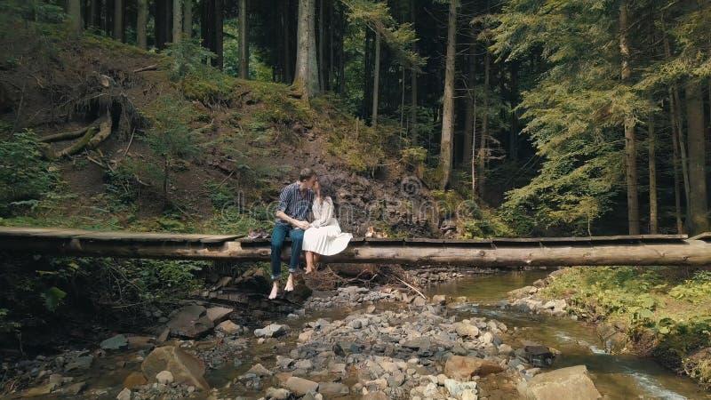 Man och kvinna som ?r f?r?lskade p? en bro ?ver floden i skog arkivfoton