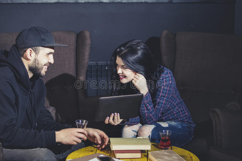 Man och kvinna som är härliga och som är lyckliga med minnestavlan och böckerna royaltyfria foton