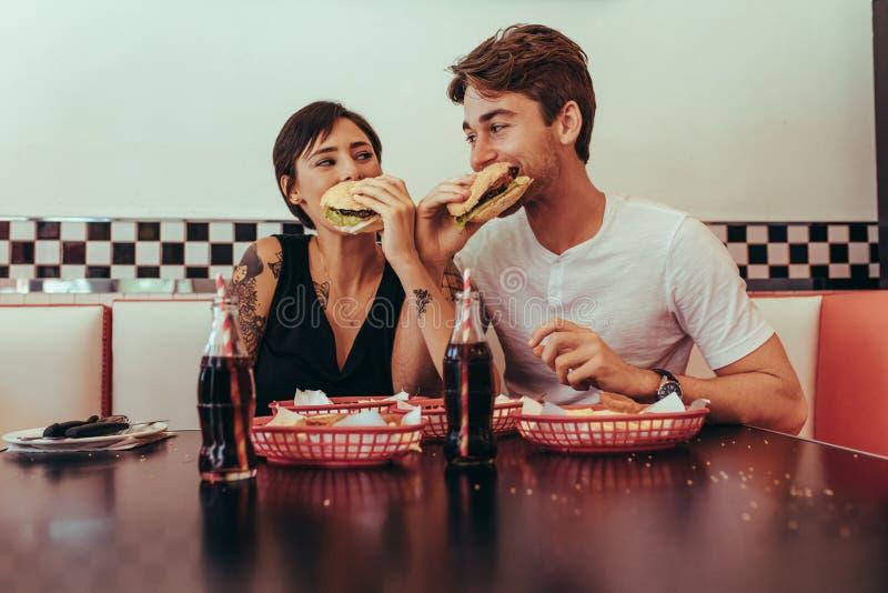 Man och kvinna som äter hamburgare på en restaurang fotografering för bildbyråer