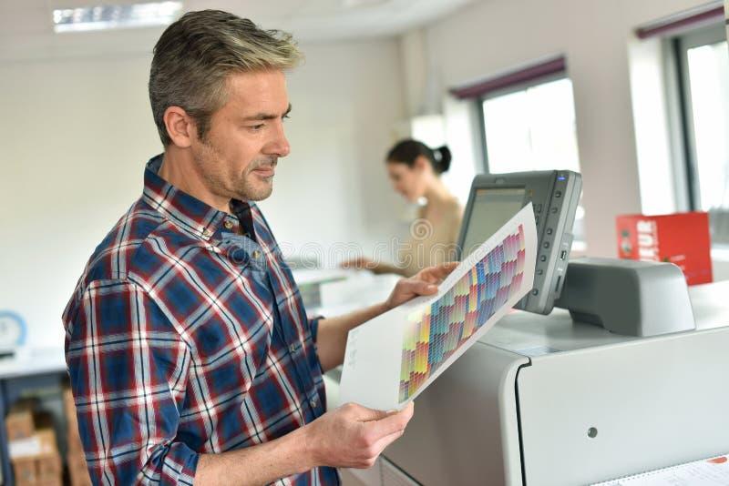 Man och kvinna som arbetar i printingkontor arkivfoto