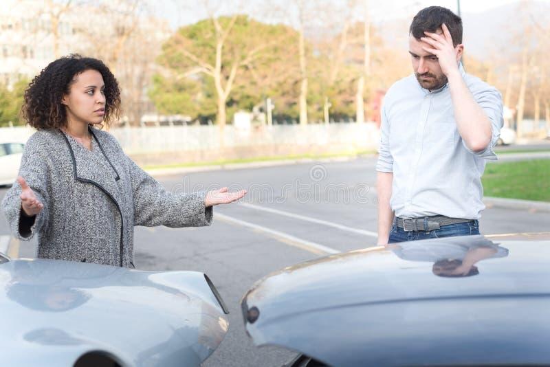 Man och kvinna som argumenterar efter dålig bilkrasch arkivfoto