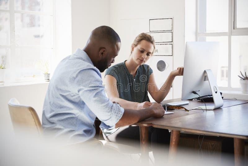 Man och kvinna som diskuterar dokument på hennes skrivbord i ett kontor arkivfoto