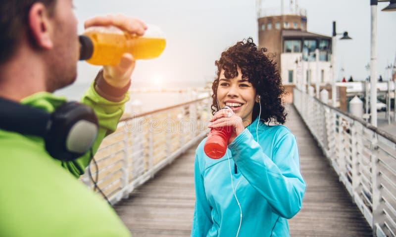 Man och kvinna som dricker energidrinken från flaskan efter konditionsportövning arkivfoto