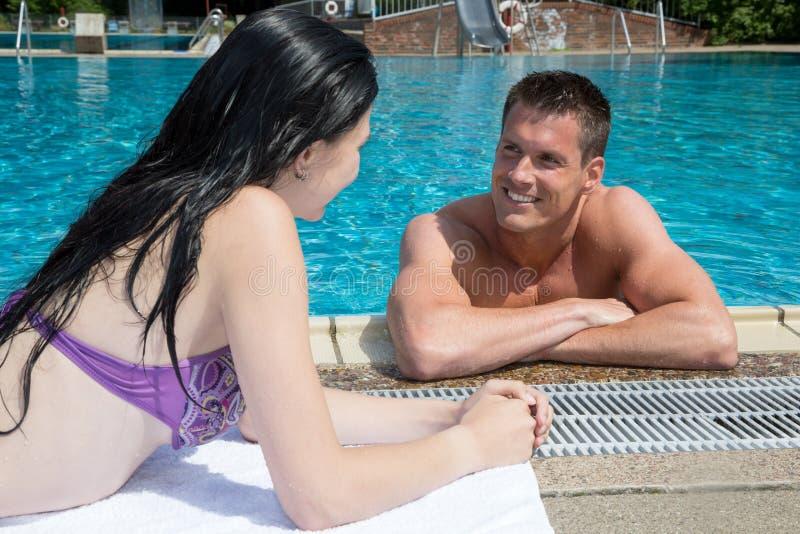 Man och kvinna som flörtar på simbassängen royaltyfri foto