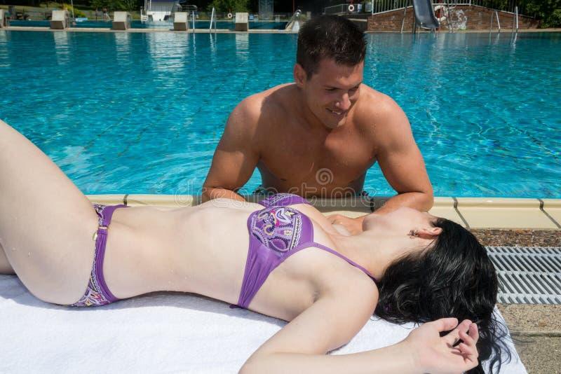 Man och kvinna som flörtar på simbassängen royaltyfri fotografi