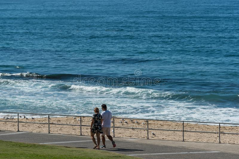 Man och kvinna som går på Cronulla strandpromenad arkivfoto