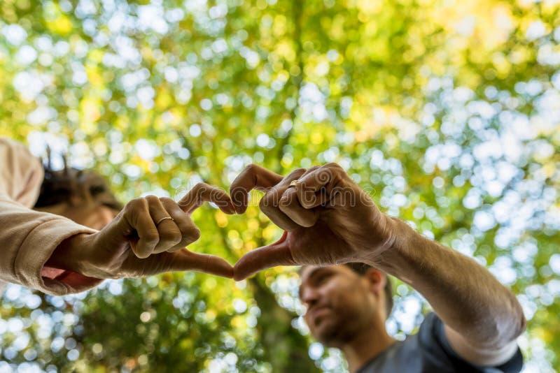 Man och kvinna som gör en delad hjärta att göra en gest arkivbilder