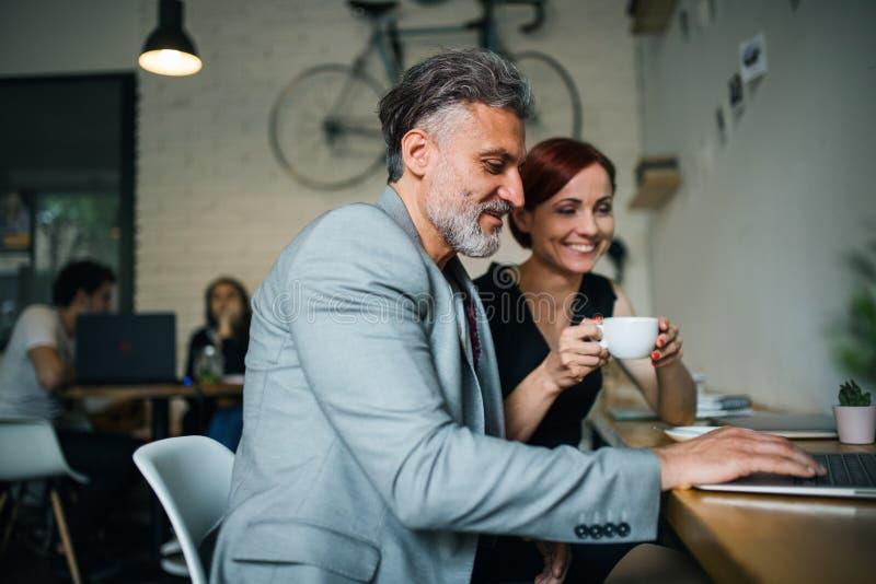 Man och kvinna som har affärsmöte i ett kafé, genom att använda bärbara datorn arkivfoton
