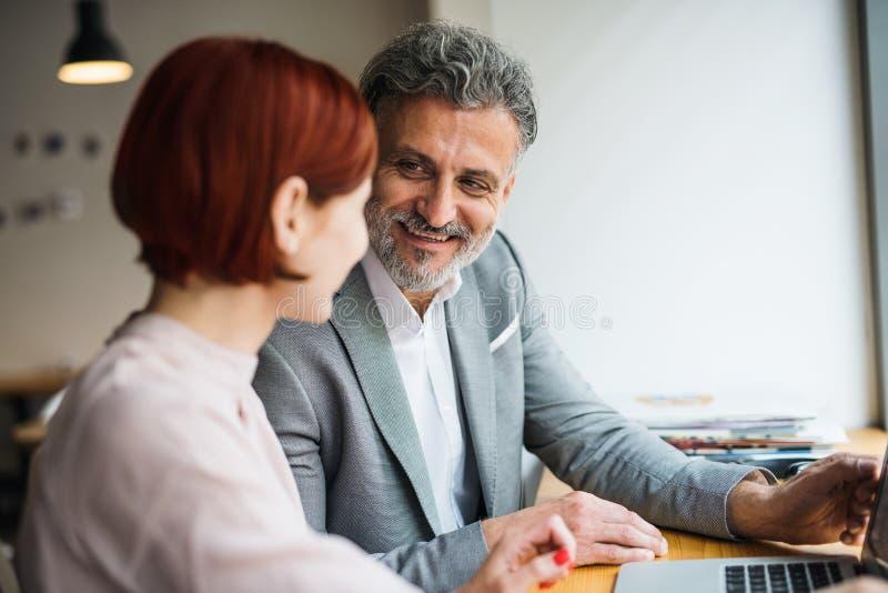 Man och kvinna som har affärsmöte i ett kafé, genom att använda bärbara datorn arkivbilder