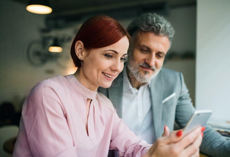 Man och kvinna som har affärsmöte i ett kafé, genom att använda smartphonen royaltyfri fotografi
