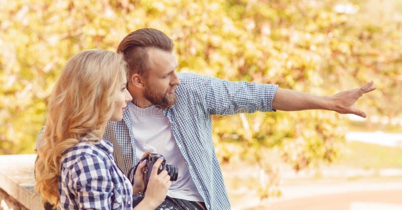 Man och kvinna som har det utomhus- datumet Flickaintelligens en fotokamera och hennes pojkv?n arkivfoto
