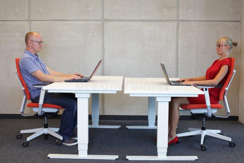 Man och kvinna som i regeringsställning arbetar i korrekt sammanträdeställing med bärbara datorer på skrivbord arkivbilder