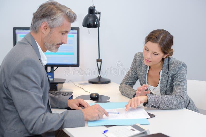 Man och kvinna som i regeringsställning diskuterar skrivbordsarbete royaltyfri bild